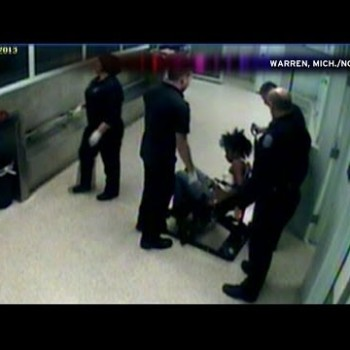 Snapshot of video showing Michigan cop cutting hair weave right out of prisoner's head.