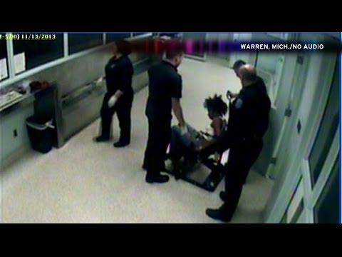 Snapshot of video showing Michigan cop cutting a woman's hair weave right out of prisoner's head.